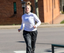 "First-year student Lainie Baumgardner, of Waxhaw, runs on Appalachian State University's campus Nov. 18 with her mask at the ready. She is a member of App State's track and field team. It's important to keep up physical activity throughout the winter for mental and physical health and immune system support, says App State's Dr. Rebecca ""Becki"" Battista, an Exercise Is Medicine Ambassador and a board member of the Physical Activity Alliance. Photo by Marie Freeman"