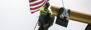 Workers place American and Appalachian flag on ceremonial beam