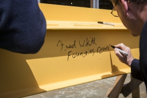 Founding Dean Fred Whitt signs the beam